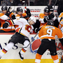 Calgary Flames' David Jones, left, gets thrown into the boards at the Philadelphia Flyers' bench by Steve Downie, right, during the third period of an NHL hockey game, Saturday, Feb. 8, 2014, in Philadelphia. The Flyers won 2-1 The Associated Press