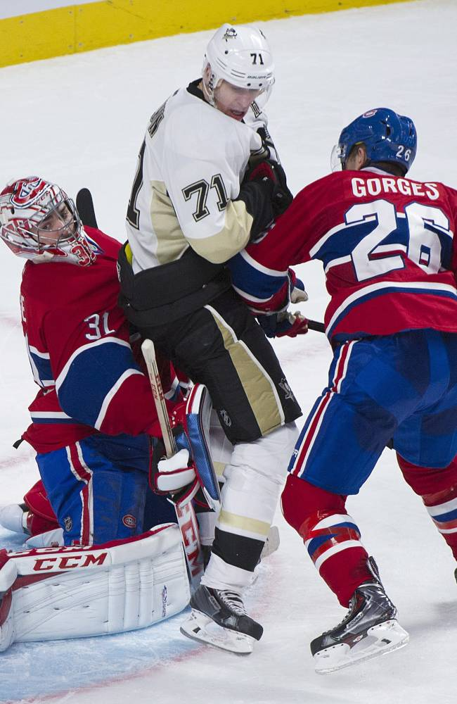 Pittsburgh Penguins center Evgeni Malkin, center, is sandwiched between Montreal Canadiens goaltender Carey Price, left, and defenseman Josh Gorges during second-period NHL hockey game action in Montreal, Saturday, Nov. 23, 2013