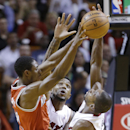 Milwaukee Bucks guard Brandon Knight, left, passes past Miami Heat forward Udonis Haslem, center, and guard Toney Douglas during the first half of an NBA basketball game on Wednesday, April 2, 2014, in Miami The Associated Press