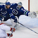 Montreal Canadiens' Max Pacioretty, lower left, scores the tying goal against Vancouver Canucks' goalie Ryan Miller as Yannick Weber, of Switzerland, stretches in vain to stop the puck during the third period of an NHL hockey game, Thursday, Oct. 30, 2014