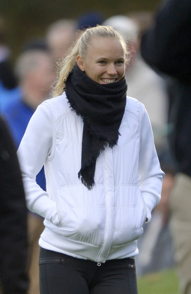 Tennis player Caroline Wozniacki walks the course as she follows Rory McIlroy, of Northern Ireland, during the second round of the Northwestern Mutual World Challenge golf tournament at Sherwood Country Club, Friday, Dec. 6, 2013, in Thousand Oaks, Calif