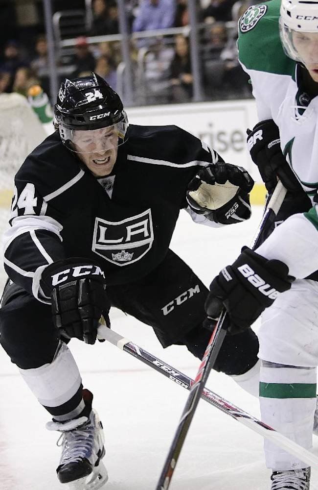 Los Angeles Kings' Colin Fraser, center, defends Dallas Stars' Antoine Roussel, of France, during the third period of an NHL hockey game on Monday, Dec. 23, 2013, in Los Angeles. The Stars won 5-2