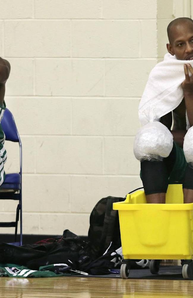Boston Celtics guard Keith Bogans, right, ices down as he sits with guard Rajon Rondo during NBA basketball training camp at Salve Regina University, Tuesday, Oct. 1, 2013, in Newport, R.I