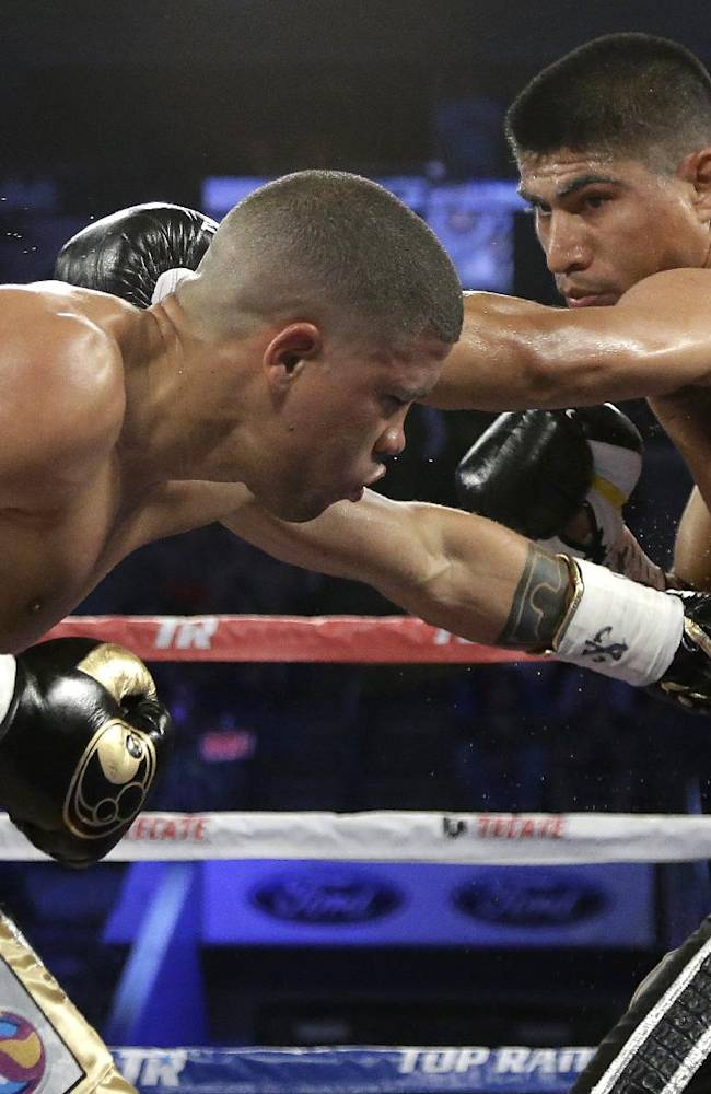 Juan Manuel Lopez, left, of Puerto Rico and Miguel Angel Garcia, right, exchange blows in the third round of their World Boxing Organization featherweight title fight boxing match Saturday, June 15, 2013, in Dallas. Garcia won the fight in the fourth round by technical knock out