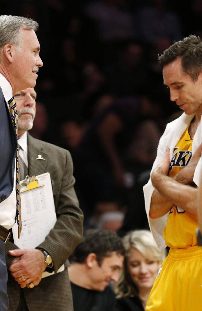Los Angeles Lakers' Steve Nash looks down while talking with coach Mike D'Antoni, left, as athletic trainer Gary Vitti, left rear, stands with them along with Steve Blake, right, while officials review a call at the end of the first half of an NBA basketball game between the Lakers and the Utah Jazz in Los Angeles, Tuesday, Feb. 11, 2014