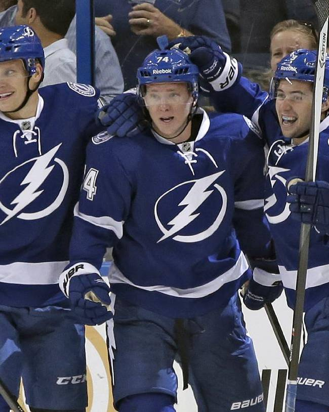 Tampa Bay Lightning left wing Ondrej Palat (74), of the Czech Republic, center, celebrates with teammates right wing Richard Panik (71), of Slovakia, left, and center Tyler Johnson, right, after scoring against the Nashville Predators during the first period of an NHL preseason hockey game Thursday, Sept. 19, 2013, in Tampa, Fla