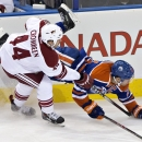 Arizona Coyotes B.J. Crombeen (44) checks Edmonton Oilers Andrew Ference (21) during third period NHL hockey action in Edmonton, on Sunday, Nov. 16, 2014 The Associated Press