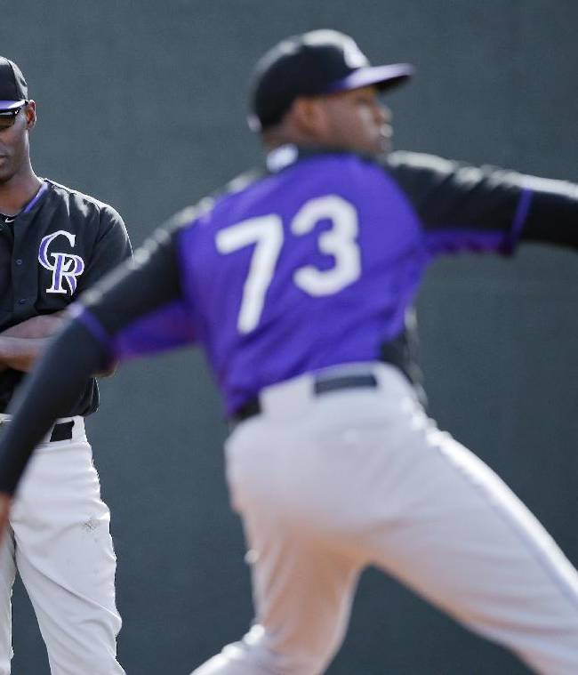 Colorado Rockies starting pitcher LaTroy Hawkins, left, watches as pitcher Jayson Aquino, right, throws during a spring training baseball practice, Friday, Feb. 21, 2014, in Scottsdale, Ariz