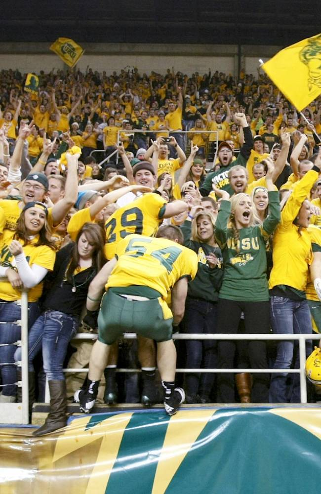 File - In this Dec. 14, 2012, file photo, North Dakota State players climb into the stands to celebrate with fans after defeating Georgia Southern in an FCS Championship semifinal college football game at the Fargodome in Fargo, N.D. ESPN is taking its College GameDay show to Fargo on Saturday, Sept. 21, 2013,  for North Dakota State's NCAA college football game game against Delaware State. Some Bison fans are ecstatic while others are grumbling about ESPN setting up downtown near the Fargo Theatre instead of the Fargodome, where dozens of green and yellow coach buses and other homemade party wagons tailgate. (