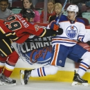 Edmonton Oilers' Nail Yakupov, right, from Russia, dodges a check from Calgary Flames' Deryk Engelland during the second period of an NHL preseason hockey game in Calgary, Alberta, Sunday, Sept. 21, 2014 The Associated Press