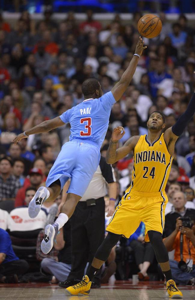 Los Angeles Clippers guard Chris Paul, left, puts up a shot as Indiana Pacers forward Paul George defends during the first half of an NBA basketball game, Sunday, Dec. 1, 2013, in Los Angeles