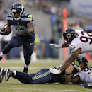 Seattle Seahawks running back Christine Michael, left, jumps over a teammate as Chicago Bears defensive tackle Stephen Paea moves in during the first half of a preseason NFL football game, Friday, Aug. 22, 2014, in Seattle The Associated Press