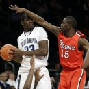 Villanova's Daniel Ochefu (23) is defended by St. John's Sir'Dominic Pointer (15) and Jakarr Sampson, bottom, during the first half of an NCAA college basketball game at the Big East Conference tournament, Wednesday, March 13, 2013, in New York. (AP Photo/Frank Franklin II)