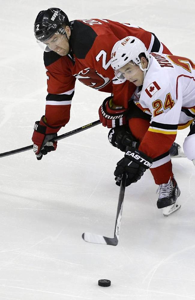 New Jersey Devils' Marek Zidlicky (2), of the Czech Republic chases the puck with Calgary Flames'  Jiri Hudler (24), of the Czech Republic, during the third period of an NHL hockey game in Newark, N.J., Monday, April 7, 2014. The Flames won 1-0