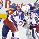 New York Rangers' Ryan McDonagh (27) and Edmonton Oilers' Matt Hendricks (23) battle in front of goalie Henrik Lundqvist (30) during second period of an NHL hockey game in Edmonton, Alberta, Sunday, Dec, 14, 2014 The Associated Press