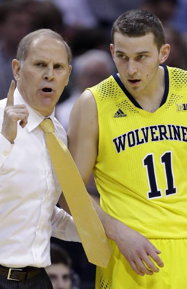Michigan head coach John Beilein, left, talks to Michigan guard Nik Stauskas (11) in the first half of an NCAA college basketball game against Michigan State in the championship of the Big Ten Conference tournament on Sunday, March 16, 2014, in Indianapolis