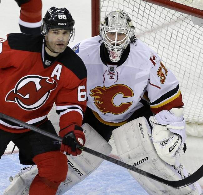New Jersey Devils' Jaromir Jagr (68), of the Czech Republic, plays in front of Calgary Flames goalie Karri Ramo (31), of Finland, during the third period of an NHL hockey game in Newark, N.J., Monday, April 7, 2014. The Flames won 1-0