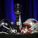 The Lombardi Trophy sits behind two helmets before a joint coaches news conference for NFL Super Bowl XLIX football game Friday, Jan. 30, 2015, in Phoenix. (AP Photo/David J. Phillip)