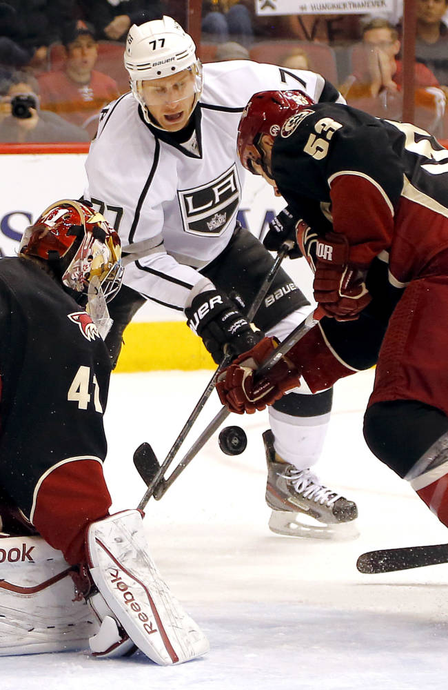 Phoenix Coyotes' Derek Morris, right, and goalie Mike Smith, left, try to keep the puck from Los Angeles Kings' Jeff Carter during the first period of an NHL hockey game, Tuesday, Oct. 29, 2013, in Glendale, Ariz