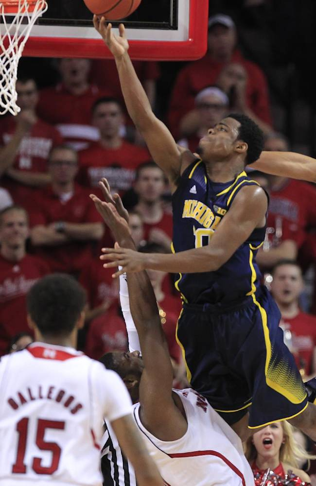 Michigan's Derrick Walton Jr. scores the Wolverines' final basket on a give-and-go play that ended with a layup over Nebraska's Leslee Smith, bottom, in the second half of an NCAA college basketball game in Lincoln, Neb., Thursday, Jan. 9, 2014. Walton was fouled on the play but missed the free throw. Michigan won 71-70