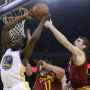 Golden State Warriors forward Draymond Green (23) grabs a rebound next to Cleveland Cavaliers center Tyler Zeller, right, during the first half of an NBA basketball game on Friday, March 14, 2014, in Oakland, Calif. (AP Photo/Marcio Jose Sanchez)