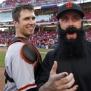 San Francisco Giants' Buster Posey celebrates with pitcher Brian Wilson after they defeated the Cincinnati Reds 6-4 in Game 5 of the National League division baseball series, Thursday, Oct. 11, 2012, in Cincinnati.  The Giants won the final three games, all in Cincinnati, and advanced to the NL championship series. (AP Photo/David Kohl)
