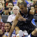 Philadelphia 76ers' Evan Turner, left, tries to hang onto a loose ball as Orlando Magic's Arron Afflalo pressures during the first half of an NBA basketball game, Tuesday, Dec. 3, 2013, in Philadelphia. (AP Photo/Matt Slocum)