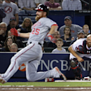 Atlanta Braves catcher Evan Gattis, right, watches his throw to pitcher Jordan Walden after chasing down a wild pitch as Walden covers home plate to tag out Washington Nationals' Adam LaRoche, right, as he tries to beat the throw in the seventh inning of