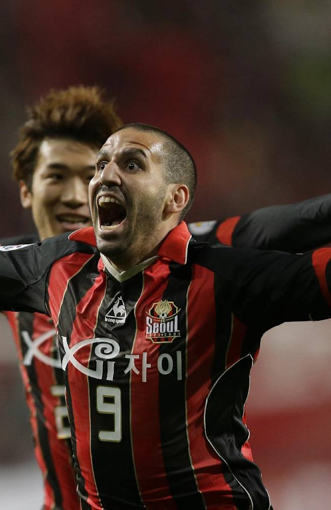 South Korea's FC Seoul Sergio Escudero, foreground, celebrates his goal with Go Yohan after scoring against China's Guangzhou Evergrande during the first leg of the 2013 Asian Champions League final against South Korea's club FC Seoul at Seoul World Cup Stadium in Seoul, South Korea, Saturday, Oct. 26, 2013
