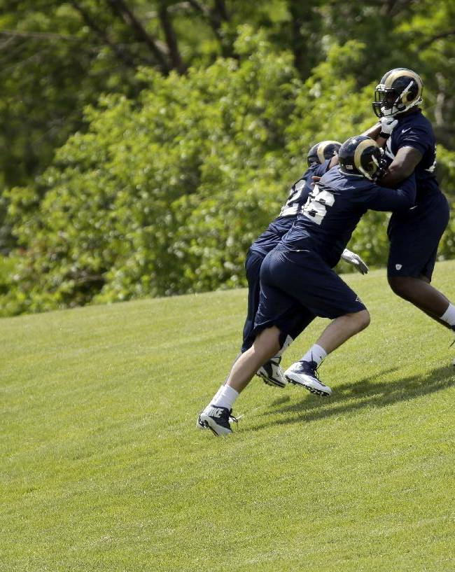 St. Louis Rams rookie offensive lineman Greg Robinson, right, a first-round draft pick, is pushed up a hill by teammates Mitchell Van Dyk, front left, and Abasi Salimu during the team's NFL football rookie camp Friday, May 16, 2014, in St. Louis