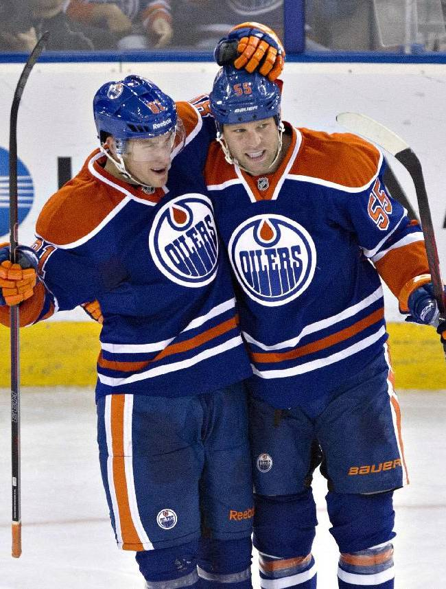 Edmonton Oilers' Taylor Fedun (81) and Ben Eager (55) celebrate a goal against the New York Rangers during the second period of an NHL hockey preseason game, Tuesday, Sept. 24, 2013, in Edmonton, Alberta