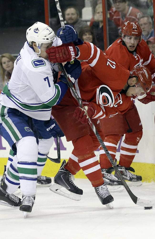 Carolina Hurricanes' Eric Staal (12) and Vancouver Canucks' David Booth (7) struggle for possession of the puck during the first period of an NHL hockey game in Raleigh, N.C., Sunday, Dec. 1, 2013. Vancouver won 3-2