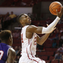Oklahoma guard Buddy Hield, right, shoots in front of Northwestern State guard Zeek Woodley (23) in the second half of an NCAA college basketball game in Norman, Okla., Sunday, Nov. 23, 2014. Oklahoma won 90-68. (AP Photo/Sue Ogrocki)