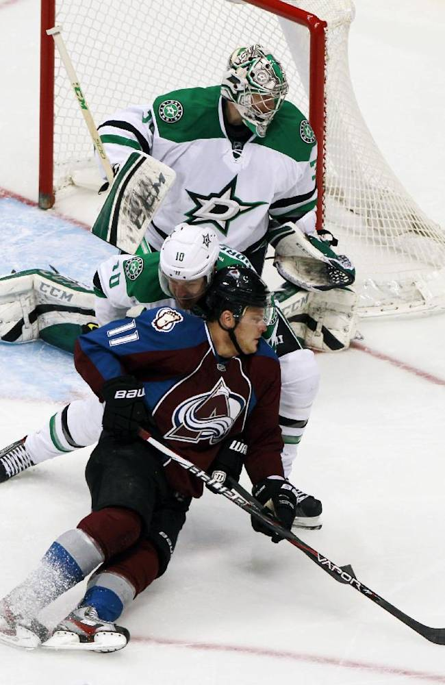 Colorado Avalanche left wing Jamie McGinn, front, is knocked down after redirecting a shot by Dallas Stars center Shawn Horcoff, center, as goalie Kari Lehtonen, back, of Finalnd, stops the puck in the second period of an NHL hockey game in Denver on Monday, Dec. 16, 2013