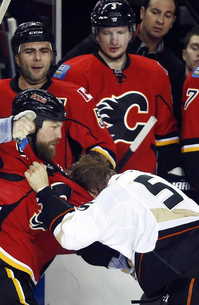 Anaheim Ducks' Bryan Allen, right, fights with Calgary Flames' Brian Mcgrattan during the first period of an NHL hockey game in Calgary, Alberta, Wednesday, March 12, 2014