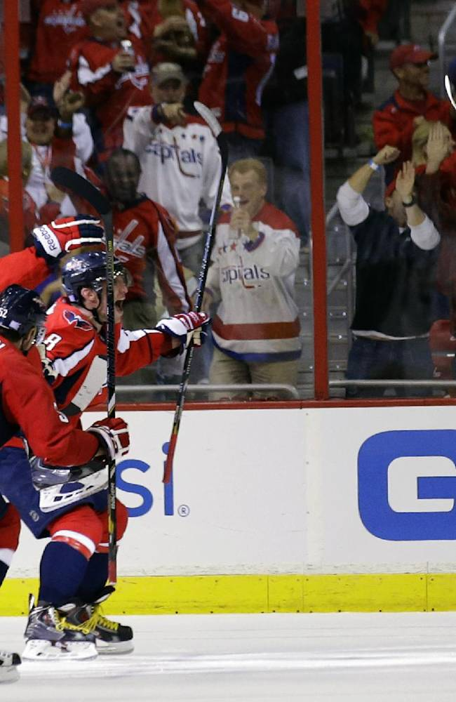 Washington Capitals center Nicklas Backstrom, right, from Sweden, celebrates his goal to tie an NHL hockey game as teammates skate to him in the third period against the Calgary Flames, Thursday, Oct. 3, 2013, in Washington. The Capitals won 5-4 in a shootout
