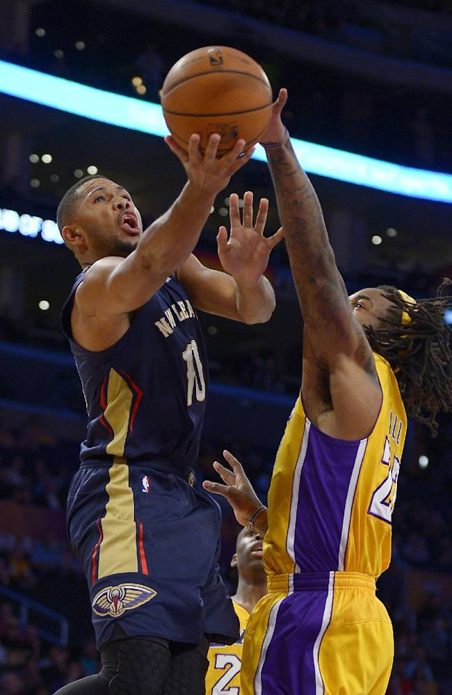 New Orleans Pelicans guard Eric Gordon, left, puts up a shot as Los Angeles Lakers center Jordan Hill defends during the first half of an NBA basketball game, Tuesday, Nov. 12, 2013, in Los Angeles