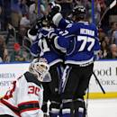New Jersey Devils goalie Martin Brodeur (30) reacts as Tampa Bay Lightning defenseman Mike Kostka (21) celebrates his goal with defenseman Victor Hedman (77), of Sweden, and others during the second period of an NHL hockey game Saturday, March 15, 2014, in Tampa, Fla. (AP Photo/Brian Blanco)