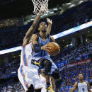 Memphis Grizzlies guard Mike Conley (11) goes up for a shot in front of Oklahoma City Thunder forward Serge Ibaka (9) in the second quarter of Game 2 of an opening-round NBA basketball playoff series in Oklahoma City, Monday, April 21, 2014. (AP Photo/Sue Ogrocki)