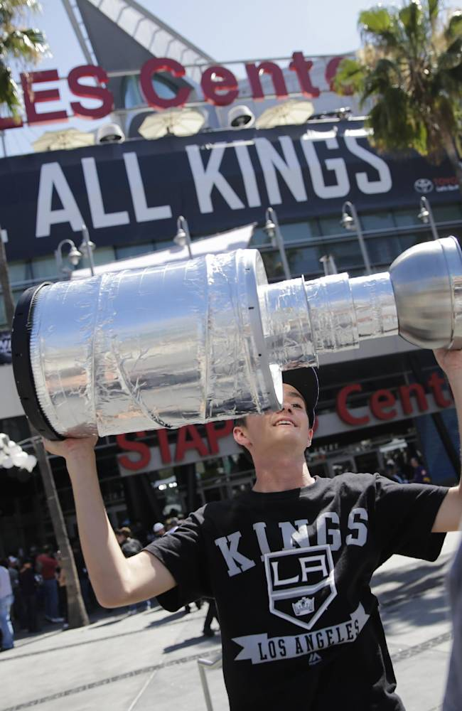 Los Angeles Kings fan Jarrod Romero, of Culver City, Calif., raises a trophy before the Kings face the New York Rangers in Game 5 of the Stanley Cup Final series Friday, June 13, 2014, in Los Angeles
