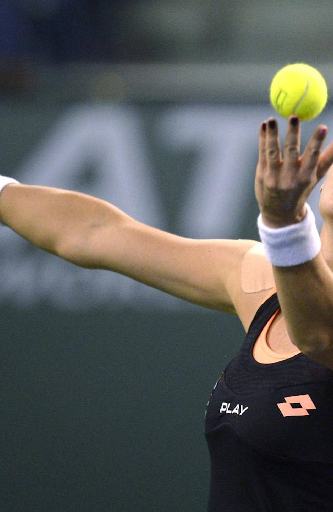 Agnieszka Radwanska, of Poland, serves to Simona Halep, of Romania, during their semifinal match at the BNP Paribas Open tennis tournament, Friday, March 14, 2014, in Indian Wells, Calif
