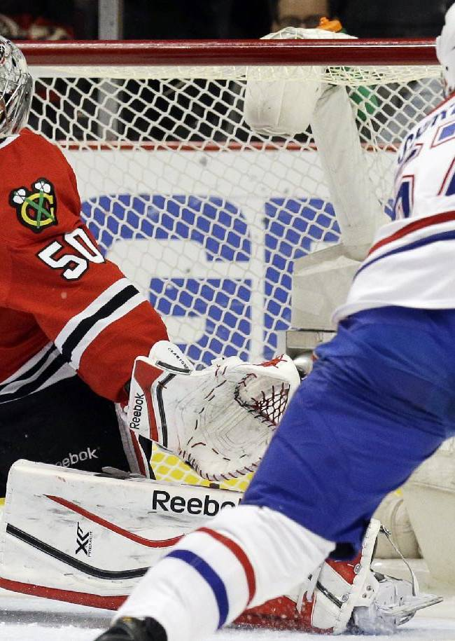 Chicago Blackhawks goalie Corey Crawford (50) blocks a shot by Montreal Canadiens' Max Pacioretty (67) during the first period of an NHL hockey game in Chicago, Wednesday, April 9, 2014