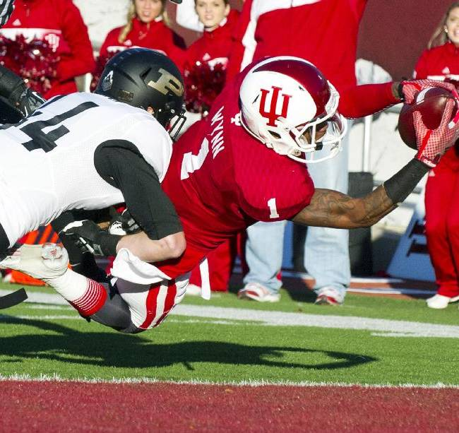 Indiana's Shane Wynn (1) dives into the end zone for a touchdown as he's hit by Purdue's Landon Feichter during the first half of an NCAA college football game Saturday, Nov. 30, 2013, in Bloomington, Ind