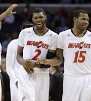 Cincinnati's Titus Rubles (2), Jermaine Sanders (15) and Troy Caupain (10) celebrate the team's 61-58 win over Central Florida in an NCAA college basketball game in the quarterfinals of the American Athletic Conference men's tournament Thursday, March 13, 2014, in Memphis, Tenn. (AP Photo/Mark Humphrey)