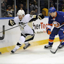 Pittsburgh Penguins' Joe Vitale (46) chases the puck around the boards ahead of New York Islanders' Matt Carkner (7) in the first period of an NHL hockey game on Tuesday, Dec. 3, 2013, in Uniondale, N.Y The Associated Press