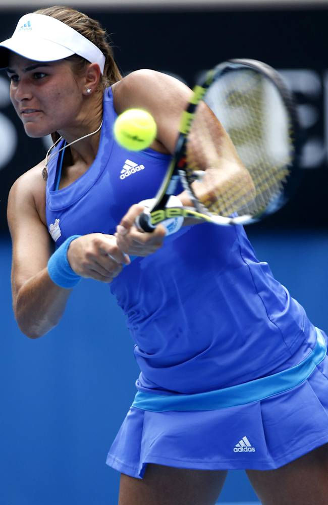 Monica Puig of Puerto Rico makes a backhand return to Flavia Pennetta of Italy during their second round match at the Australian Open tennis championship in Melbourne, Australia, Wednesday, Jan. 15, 2014