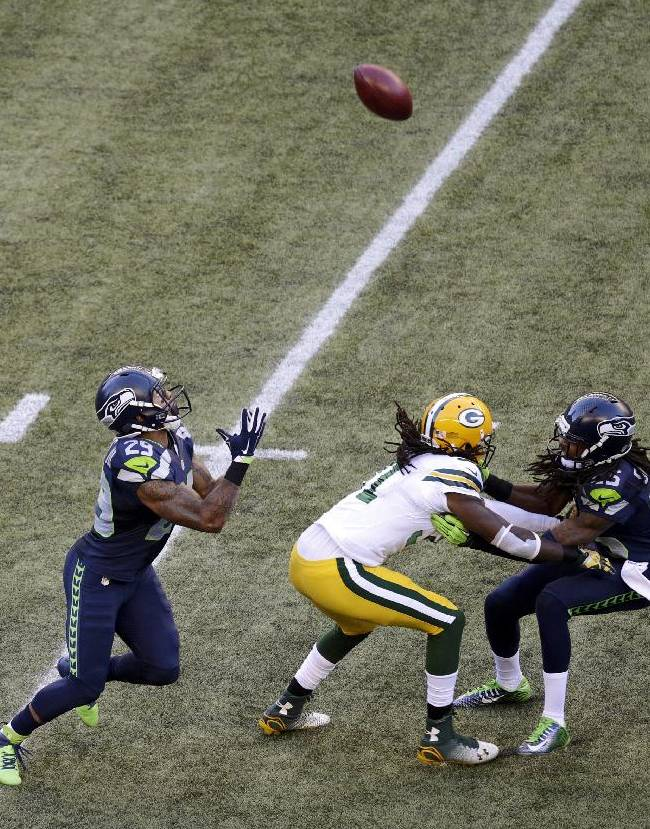 Seattle Seahawks' Earl Thomas, left, prepares to catch a punt during the first half of an NFL football game against the Green Bay Packers, Thursday, Sept. 4, 2014, in Seattle