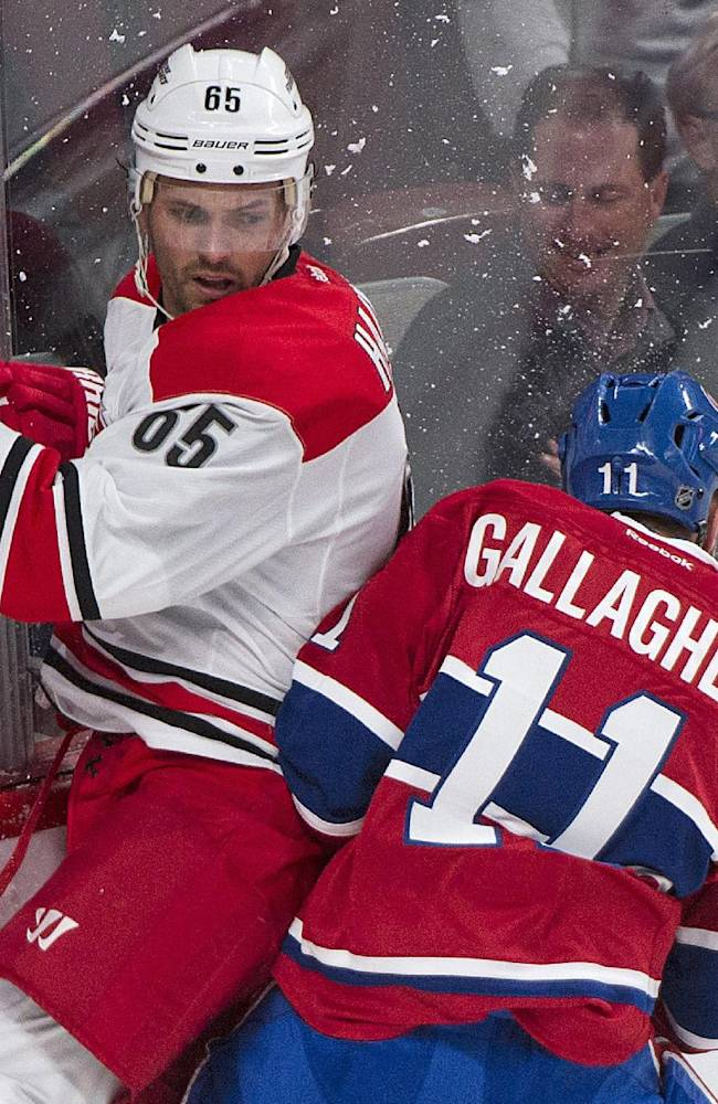 Montreal Canadiens' Brendan Gallagher, right, checks Carolina Hurricanes' Ron Hainsey into the boards during the first period of a preseason NHL hockey game Saturday, Sept. 21, 2013, in Montreal