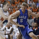 Duke forward Mason Plumlee (5) draws a foul as he drives to the basket against Virginia center Mike Tobey (10) during the first half of an NCAA college basketball game in Charlottesville, Va., Thursday, Feb. 28, 2013. (AP Photo/Steve Helber)