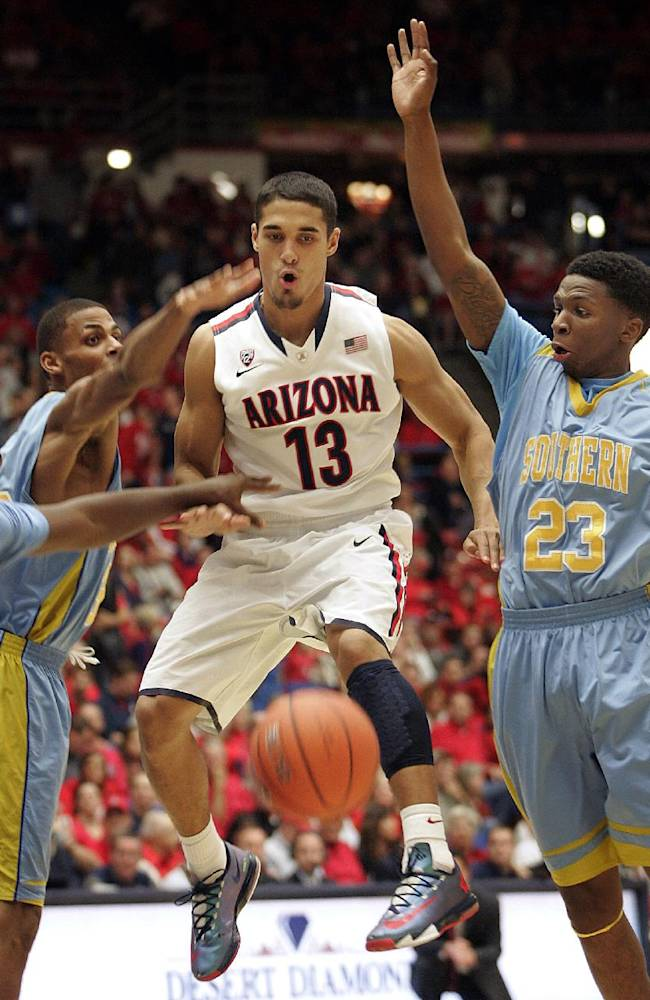 Arizona's Nick Johnson (13) is sandwiched between Southern University's Malcolm Miller, left, Javan Mitchell (44) and Yondarius Johnson (23) as they all scramble for a loose ball in the first half of an NCAA college basketball game on Thursday, Dec. 19, 2013, in Tucson, Ariz. Arizona won 69-43